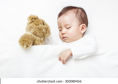 Baby sleepping with her teddy bear, new family and love concept.