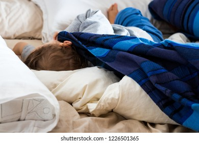 A baby sleeps and conquers the bed of his parents alone.