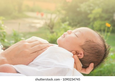 Baby sleeps on mother's hands and morning sun