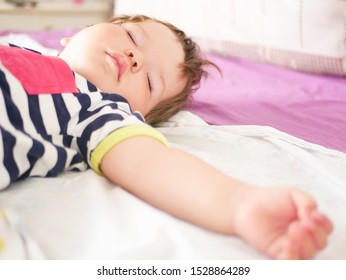 baby sleeps in parents bed. arms outstretched baby's restful sleep. close-up. child 0-1 years old. adorable lovely baby sleeps calmly in bed, has a pleasant healthy sweet dream, cared for. From