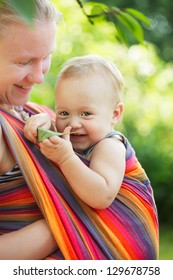 Baby in sling outdoor. Mother is carrying her child and showing nature details