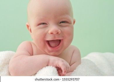 Baby smiles into the camera lens.
