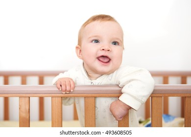 A baby is smiling in the crib and holds onto the side of the bed
