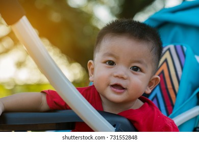 baby smiling and looking to camera outdoors in sunlight, Asian boy in the park