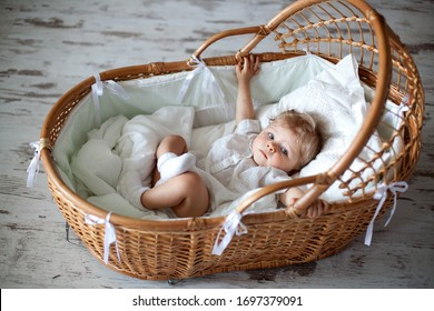 A baby with snow-white hair sits in an old cradle.