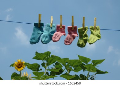 baby socks on a clothes-line with sunflower on the background