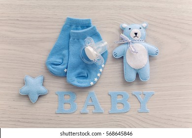 baby socks and a pacifier lying next to a toy bear