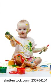 Baby soiled by paints holds brushes in hand
