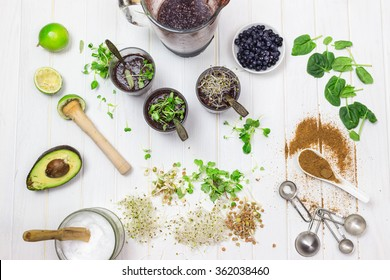 Baby spinach, blueberry cleaning smooth in a blender with ingredients ready to prepare smoothie bowl breakfast on white wooden table, rustic style