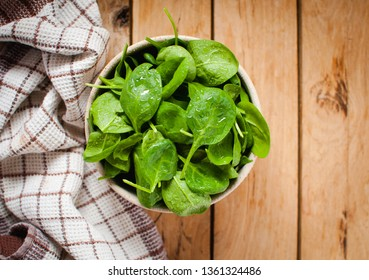 Baby spinach in a bowl on wooden table, top view