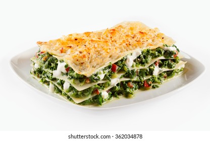 Baby spinach lasagne with mozzarella alternating with layers of traditional Italian noodles served on a square plate isolated on white