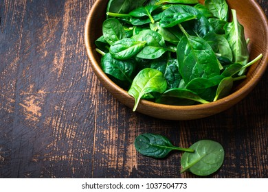 Baby spinach leaves in a bowl on dark background