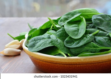 Baby spinach leaves in stoneware bowl on rustic wooden table