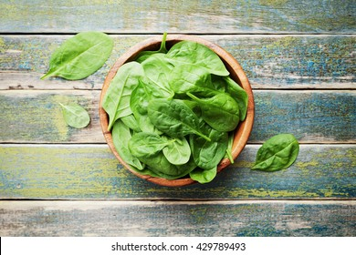 Baby spinach leaves in wooden bowl on old rustic table, organic food, top view.