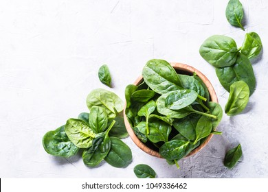 Baby spinach on gray stone table top view.