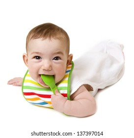 Baby with spoon in mouth looking at camera