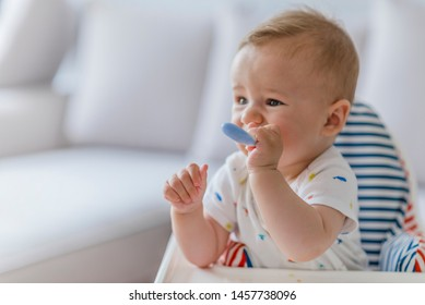 Baby with a spoon. Portrait of a baby eating with a stained face.  Healthy nutrition for kids. Happy baby eating himself with a spoon. Beautiful baby eating mashed