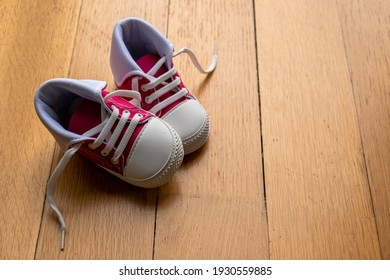 Baby sport shoes on wooden floor. Kid small size pink red sneakers, canvas booties closeup view. Space, card invitation template