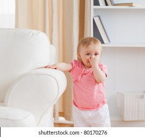 Baby standing near a sofa in the living room