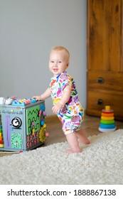 Ein Baby steht auf dem Boden und spielt mit dem belebten Würfel. Entwicklung von feinmotorischen Fähigkeiten der Hände.