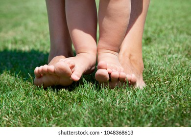 Baby standing on her mother's legs. Standing on the green grass. Learning to walk