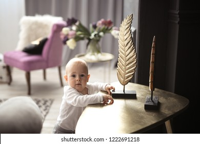 Baby stands at support and reaches out to things on the table, concept of child development and the safety of the baby in the house.