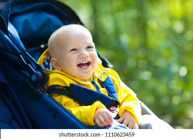 Baby in stroller on a walk in autumn park. Adorable little boy in green jacket sitting in colorful pushchair under warm blanket. Fall outdoor fun for kids. Child in buggy on winter stroll.
