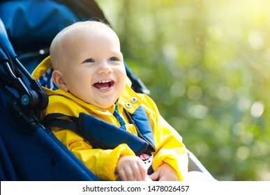Baby in stroller on a walk in autumn park. Adorable little boy in yellow jacket sitting in blue pushchair. Fall outdoor fun for kid. Child in buggy.