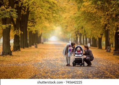 baby in a stroller with parents on an autumn walk in the park