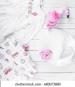 Baby stuff for girl white colors with pink drawings on a white wooden background. Slippers, sleighwoman, blouse for girls up to six months lie on a white background.