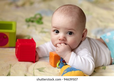 The baby sucking his finger on a bed at home
