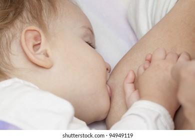 Baby sucking milk in bed