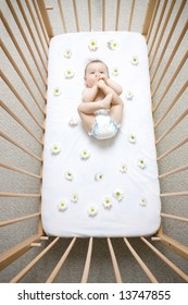 Baby sucking on feet in crib with flowered daisy sheets, caucasian/white.