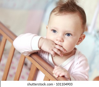 Baby sucking thumb in crib and looking. Closeup portrait of fun little girl