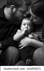 Baby sucking thumb while being kissed by loving parents. Classical black and white family photo with 4-month-old baby boy.