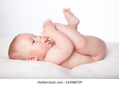 The baby sucks his toes on his own foot, replacing a pacifier