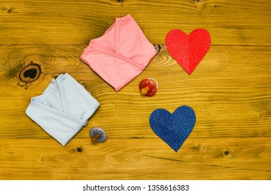Baby supplies for boy and girl and heart shape on wooden table.Baby announcement concept.Toned photo.