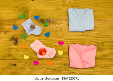 Baby supplies for  boy and girl and heart shapes on wooden table.Baby announcement concept.Toned photo.