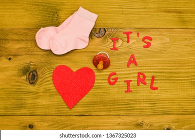 Baby supplies for baby girl and heart shape on wooden table.Toned photo.