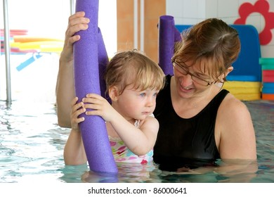 Baby swimming with mother
