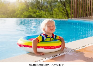 Baby in swimming pool. Little boy playing in outdoor pool. Kids learn to swim. Child with inflatable toy ring in tropical resort. Summer vacation with toddler kid. Water fun for family with children.