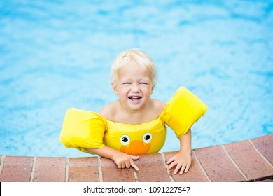 Baby in swimming pool with yellow swim aid. Child with float wings. Kid wearing floaties. Little boy playing in water during summer vacation in tropical resort.