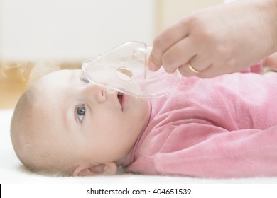 Baby taking respiratory therapy. Hand holding the mask of a nebuliser.