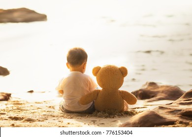 Baby and teddy bear sit together on the beach, this image can use for kid, friend, love, travel, lone and family concept