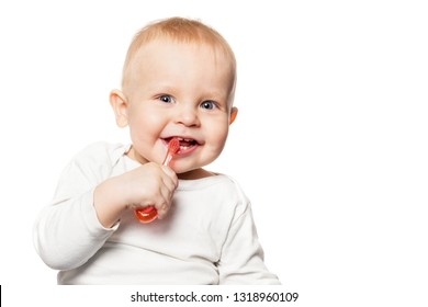 Baby teeth care. Smiling boy brushing his teeth with a toothbrush for infant. Isolated portrait