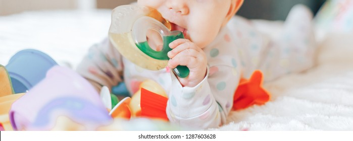 Baby Teether, Kid Bite Teething Toy in Mouth, Infant Child Growing First Tooth, Little Boy or girl Crawling on bed at home