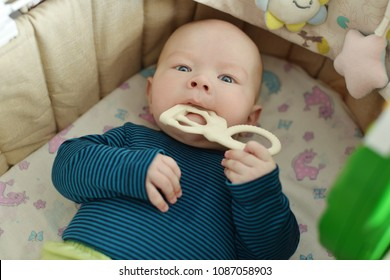 baby with teether toy in the crib