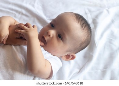 Baby teething. Baby tooth care concept. Mother checking her baby boy mouth. First signs of baby teeth come in. Infant teething pain. Free space