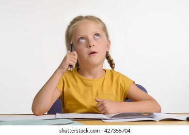Baby thinks over her homework and looks upwards with her blue eyes. She holds a pencil in her hand and it touches her temple. Dreaming little girl.
