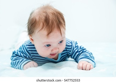 The baby is three months from birth. Baby lying on stomach lifts up on hands, holds her head, looks around. Blonde white babe in striped blouse.